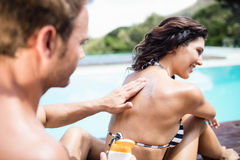 Man applying sunscreen on back of her woman  Stock Photos