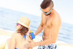 Man applying sunscreen on the back of his woman Royalty Free Stock Photo