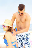 Man applying sunscreen on the back of his woman Stock Images