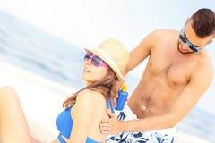 Man applying sunscreen on the back of his woman Stock Image