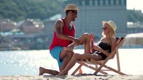 Man applying sunscreen on girlfriends leg on beach stock video