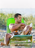 Man applying sunscreen lotion at beach Stock Photo