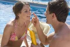 Man applying sunscreen to woman`s nose at poolside. Man applying sunscreen to woman's nose at poolside stock photo