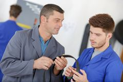 Man with apprentice holding bearing Royalty Free Stock Images