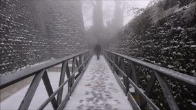 Man approach on the bridge with snow, cold winter landscape stock video footage