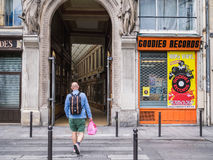 Man approaches Paris arcade; Goodies record shopfront at right Royalty Free Stock Photo