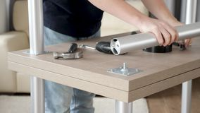 Man approaching a turned table and unscrews a leg. Disassembling furniture stock video footage