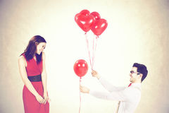 Man approaching woman giving her red heart shape balloons in a valentine`s day Stock Image