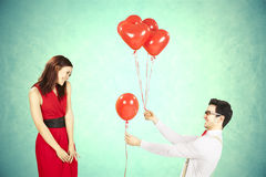 Man approaching woman giving her red heart shape balloons. Man approaching women giving her red heart shape balloons with light blue background Royalty Free Stock Photography