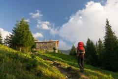 Man aproaching mountain hut Stock Photo