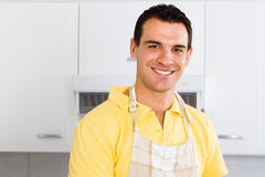 Man with apron. Young man with apron in modern kitchen Stock Photography