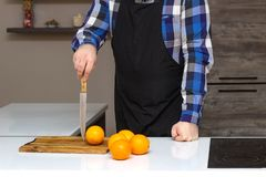 A man in an apron chef stands with a knife in the kitchen, oranges fruits are on the table, copy space, lifestyle stock image