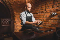 Man in apron cleaning footwear. Careful bearded man brushing the surface of leather shoes Royalty Free Stock Image