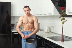 Man in an apron with a frying pan. Stock Photography