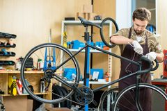 Fixing handlebars. Man in apron and gloves fixing handlebars of bicycle in workshop Stock Photography