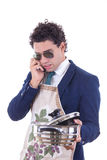 Man with an apron holding a cooking pot and talking over phone Stock Photo