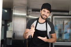A man in an apron posing in a mobile diner. He is holding a delicious chocolate ice cream. A man in an apron posing in a mobile diner. He holds a delicious Royalty Free Stock Image