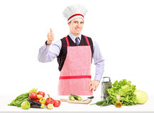 Man with apron posing with vegetables and giving a thumb up Stock Image