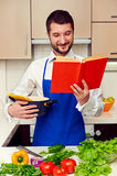 Man in apron reading the cookery book Stock Images