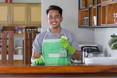 Man cleaning table. Man with apron and rubber gloves wiping wooden table in kitchen Stock Photography