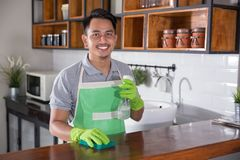 Man cleaning table. Man with apron and rubber gloves wiping wooden table in kitchen Royalty Free Stock Image