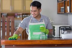 Man cleaning table. Man with apron and rubber gloves wiping wooden table in kitchen Royalty Free Stock Photo