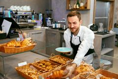Man Selling Bakery In Pastry Shop. Man In Apron Selling Fresh Bakery In Cozy Pasrty Shop. High Resolution Stock Photography