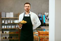 Man Selling Bakery In Pastry Shop. Man In Apron Selling Fresh Bakery In Cozy Pasrty Shop. High Resolution Royalty Free Stock Image