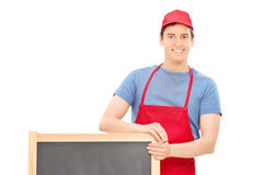 Man in apron standing behind a wooden blackboard Royalty Free Stock Image