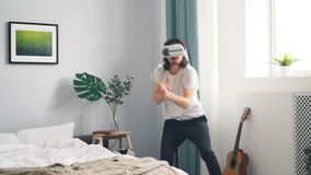 Man in ar glasses playing war video game shooting gesturing in bedroom at home. Man in ar glasses is playing war video game shooting gesturing in bedroom at home stock footage