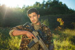 Man of Arab nationality in camouflage with a shotgun Stock Photo