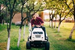 Man arbetaren som använder gräsklipparen och gräs för bitande trädgård Trädgårdmaintanancearbeten Royaltyfri Foto