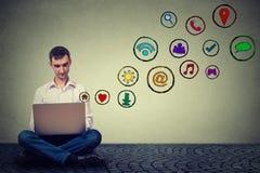 Man arbete genom att använda för massmediaapplikationen för bärbara datorn som sociala symboler flyger upp Royaltyfri Bild