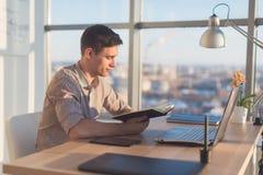 Man arbete i det moderna kontoret som ner skriver nya idéer hans anteckningsbok som söker information genom att använda den bärba Arkivfoton