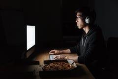Man arbete med datoren och ätapizza i mörkt rum Royaltyfria Foton
