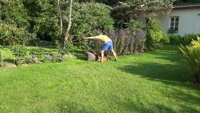 Man arbete med grässkäraren i grönt hem för blommaträdgård nära 4K stock video