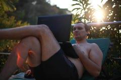 Man arbete på bärbara datorn av simbassängen under solnedgång i tropisk djungel Royaltyfri Fotografi