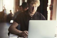 Man arbete på det soliga kontoret på bärbara datorn, medan sitta i kafét som har kaffe Begrepp av ungt affärsfolk som offentligt  arkivfoto