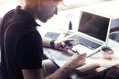 Man arbete på det soliga kontoret på bärbara datorn, medan sitta i kafét som har kaffe Begrepp av ungt affärsfolk som offentligt  royaltyfri foto