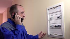 Man arbete på en säkerhetsbrytare och ringa för strömkrets lager videofilmer