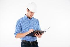 Man architect in building helmet writing in folder Royalty Free Stock Photos