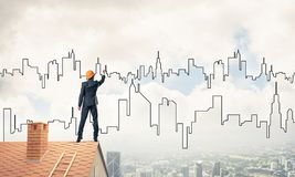 Man architect draw silhouette of modern city on blue sky. Mixed Royalty Free Stock Images