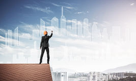 Man architect draw silhouette of modern city on blue sky. Mixed Stock Photo