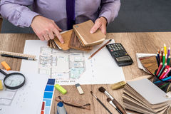 Man architect draws a house plan with color palette for furniture, stock photo