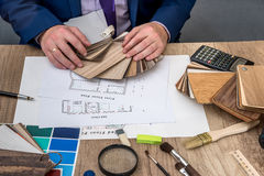 Man architect draws a house plan with color palette for  furniture, Royalty Free Stock Photo