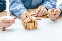 Two man one women architect draws a plan,on large sheet of paper at office desk and builds model house from wooden blocks bars. Man architect draws a plan,on stock image