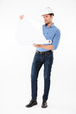 Man architect in hard hat holding and looking at blueprint. Concentrated young man architect in hard hat holding and looking at blueprint Royalty Free Stock Photos