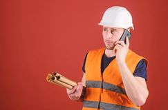 Man, architect in helmet supervises construction on phone, red background. Negotiation concept. Engineer, architect. Builder on busy face speaks on smartphone stock photos