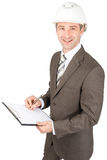 Man architect in helmet writing on document Stock Photography