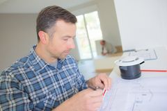 Man architect with house plan stock photography